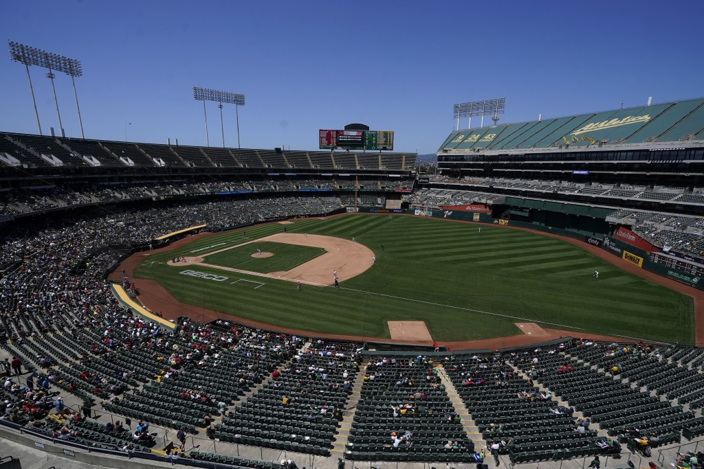 Fans watch as Oakland Athletics' James Kaprielian pitches against the Los Angeles Angels during the sixth inning of a baseball game in Oakland, Calif....