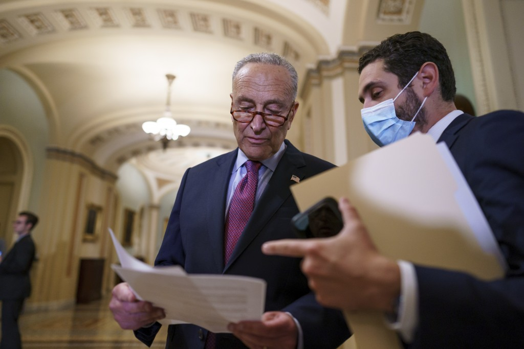 Senate Majority Leader Chuck Schumer, D-N.Y., looks over his notes as he talks to reporters about his plans for a procedural vote tomorrow on the bipa...