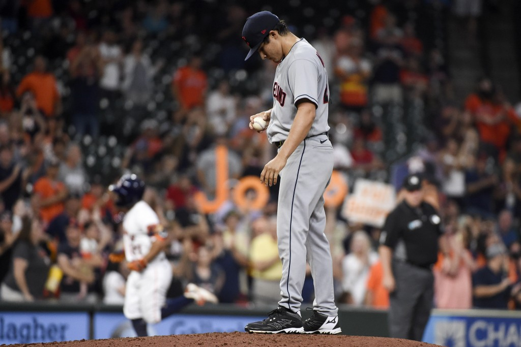 Cleveland Indians starting pitcher Eli Morgan, right, looks down as Houston Astros' Jose Altuve, left, runs the bases after hitting a solo home run du...