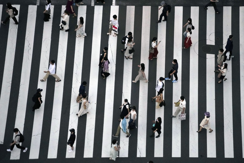 People wearing protective masks to help curb the spread of the coronavirus walk along a pedestrian crossing Thursday, July 22, 2021, in Tokyo. The Jap...
