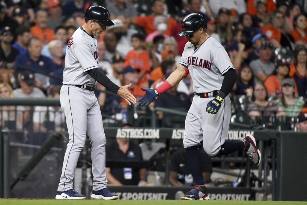 Cleveland Indians' Cesar Hernandez, right, clasps hands with third base coach Mike Sarbaugh after hitting a solo home run during the seventh inning of...