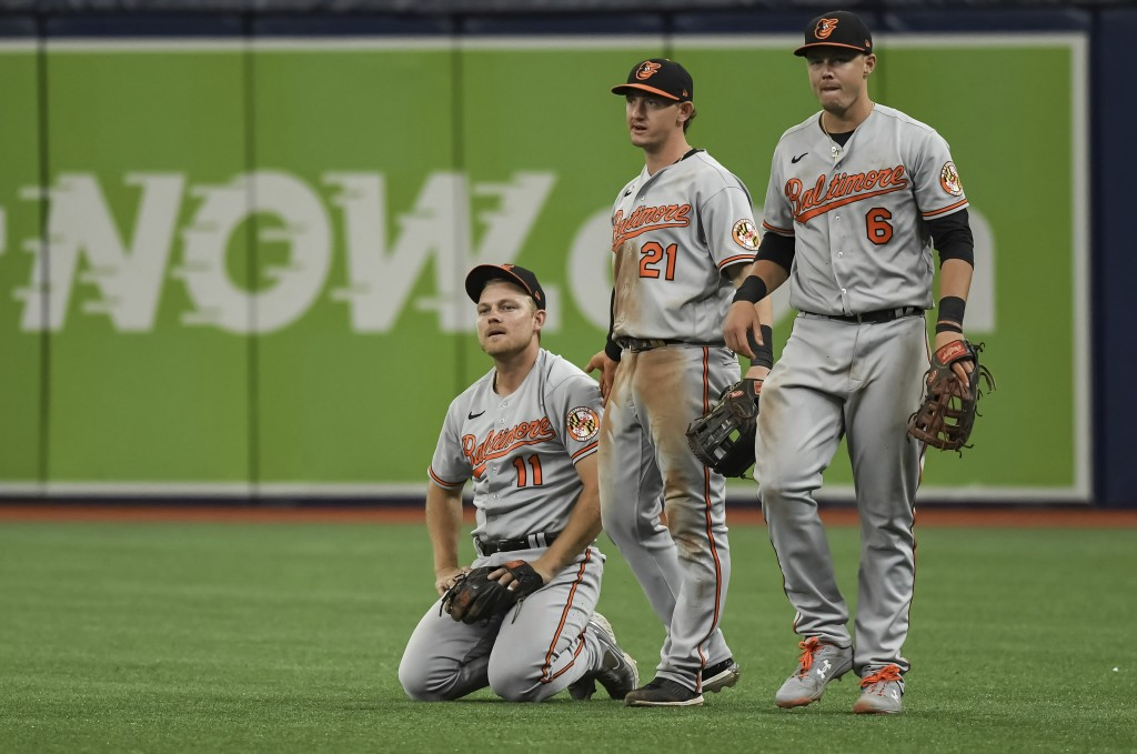 Baltimore Orioles' Pat Valaika (11), Austin Hays (21) and Ryan Mouncastle (6) react after a bloop single hit by Tampa Bay Rays' Randy Arozarena droppe...