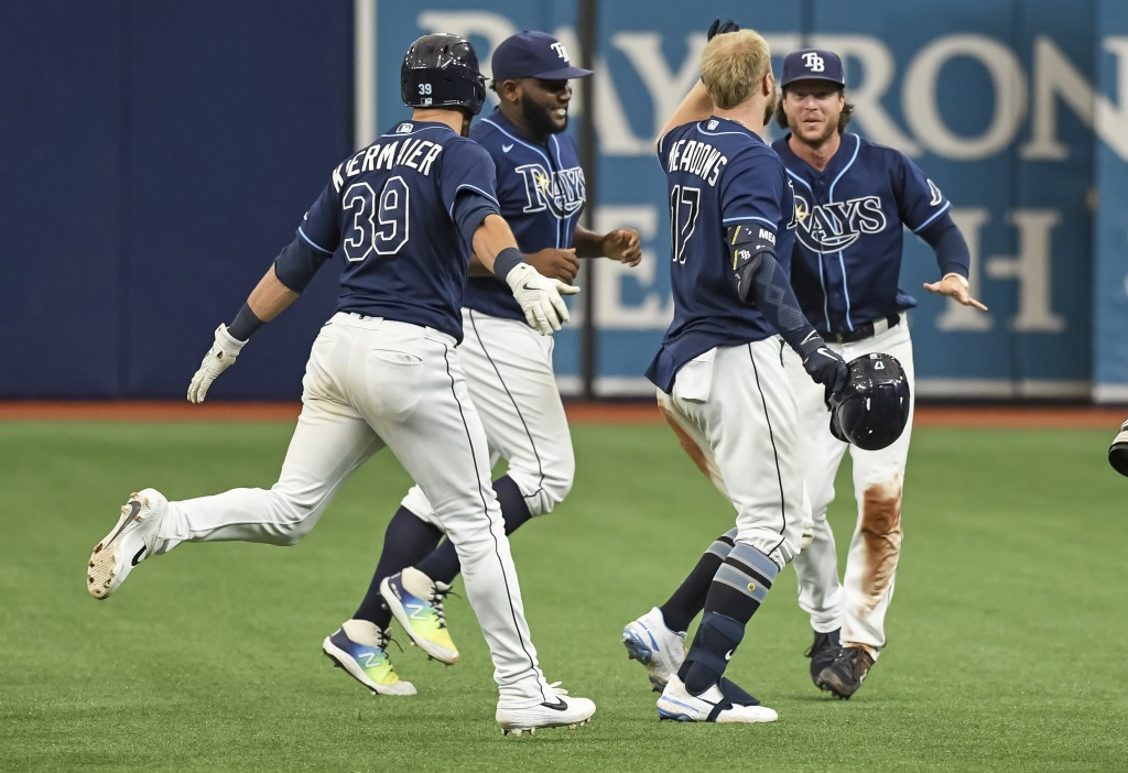 Tampa Bay Rays' Kevin Kiermaier (39), Diego Castillo and Brett Phillps, right, congratulate Austin Meadows (17) after his two-run single beat the Balt...