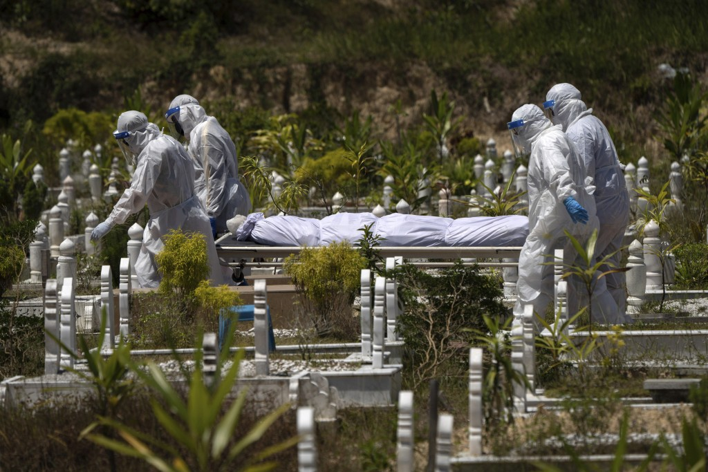 In this Feb. 5, 2021, file photo, workers wearing personal protective equipment (PPE) carry the body of a victim of the coronavirus disease at a Musli...
