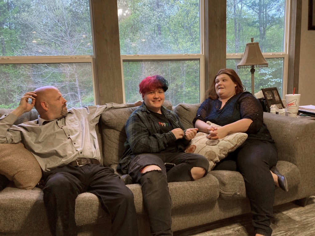 FILE - In this April 15, 2021 file photo, Andrew Bostad, center, talks with his mother, Brandi Evans and stepdad Jimmy Evans at their home in Bauxite,...
