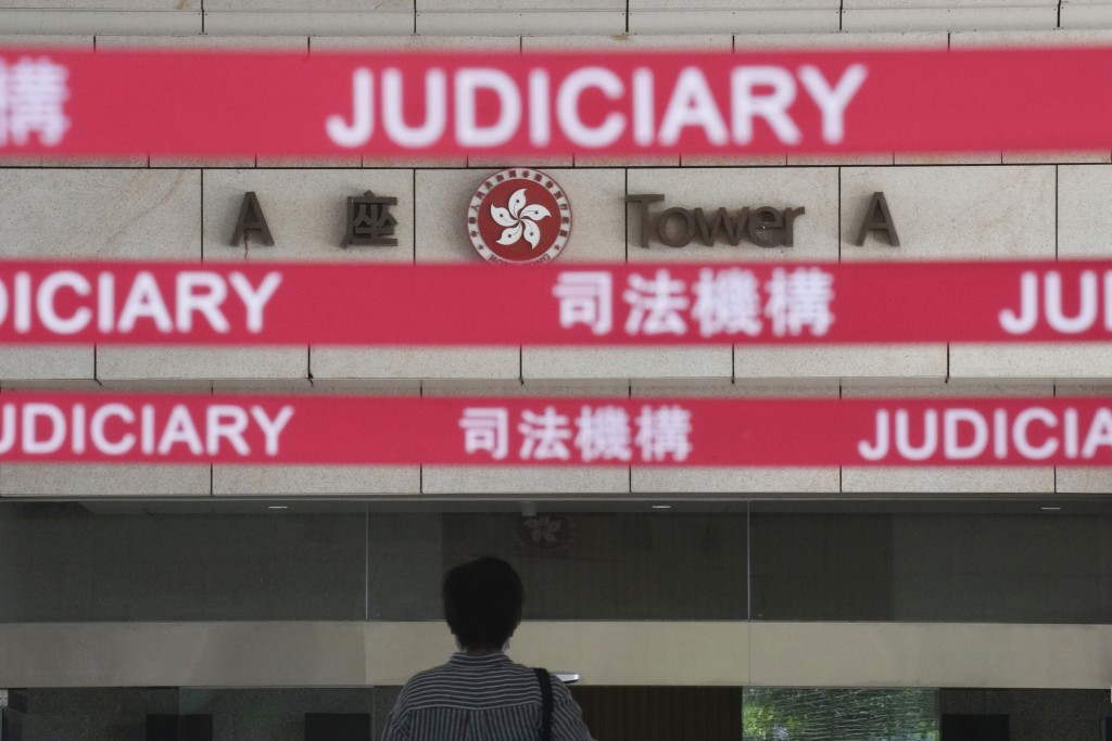 A man walks toward the main entrance to local court in Hong Kong Thursday, July 22, 2021. Hong Kong police charged two top editors and two editorial w...