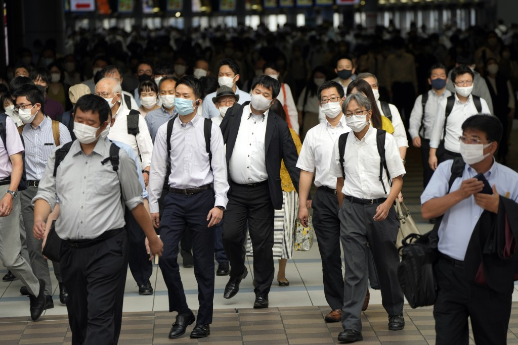 FILE - In this July 12, 2021, file commuters wearing face masks walk in a passageway during a rush hour at Shinagawa Station in Tokyo. Tokyo recorded ...