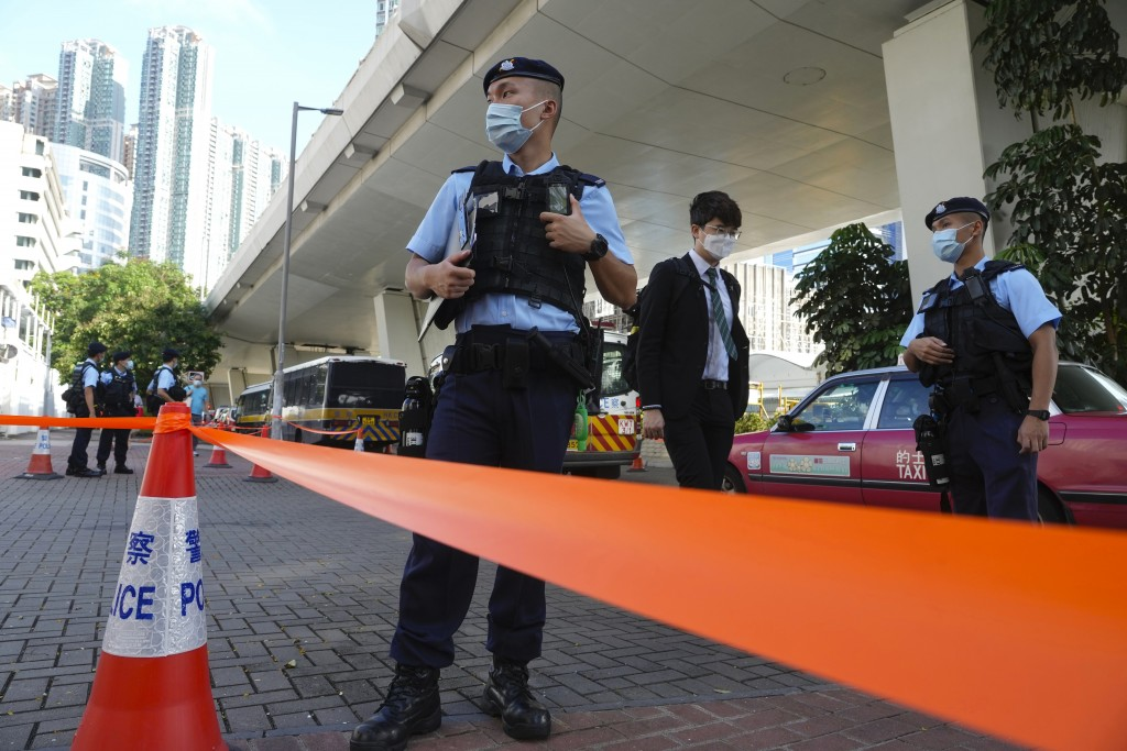 Police officers stand guard outside local court in Hong Kong Thursday, July 22, 2021. Hong Kong police charged two top editors and two editorial write...