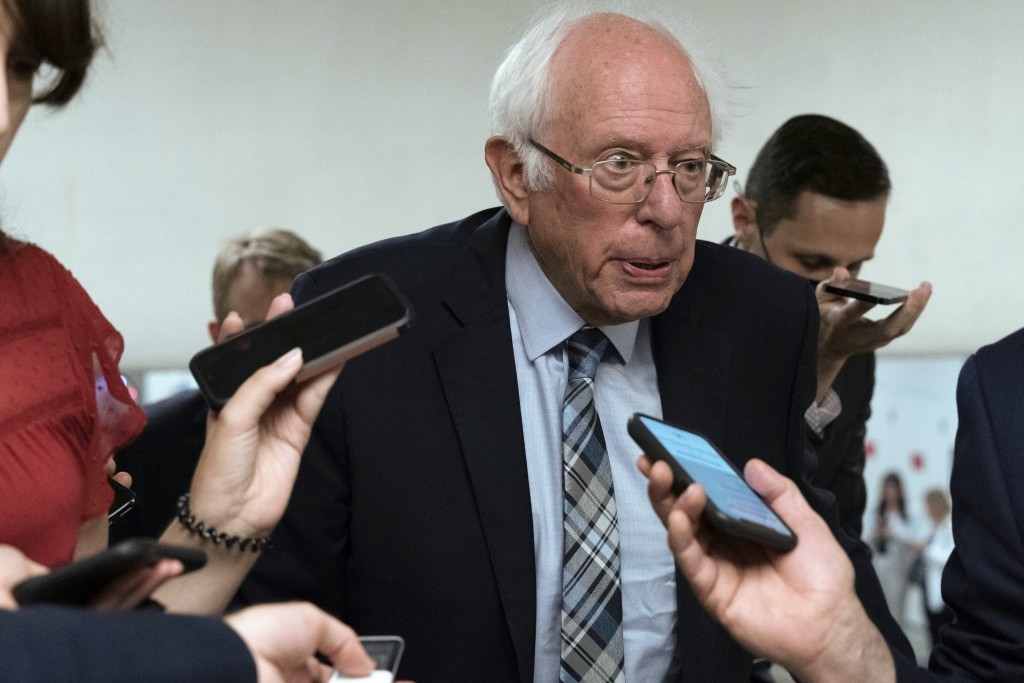 Sen. Bernie Sanders, I-Vt., talks to reporters as he walks to the senate chamber ahead of a test vote scheduled by Democratic Leader Chuck Schumer of ...