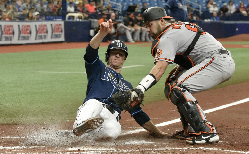 Baltimore Orioles catcher Austin Wynns, right, tags out Tampa Bay Rays' Joey Wendle at the plate during the second inning of a baseball game Wednesday...