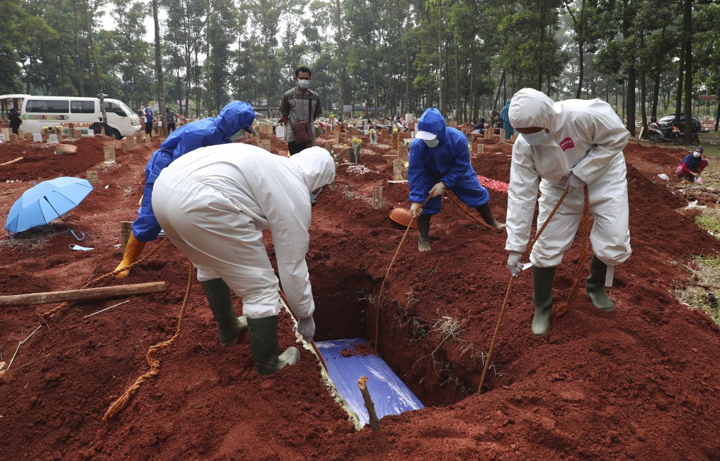 In this July 14, 2021, photo, workers in protective gear lower a coffin of a COVID-19 victim to a grave for burial at the Cipenjo Cemetery in Bogor, W...