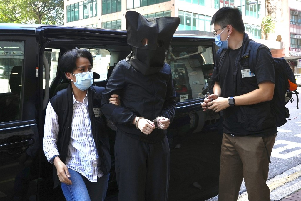 A hooded suspect is accompanied by police officers to search evidence at office in Hong Kong Thursday, July 22, 2021. Hong Kong's national security po...