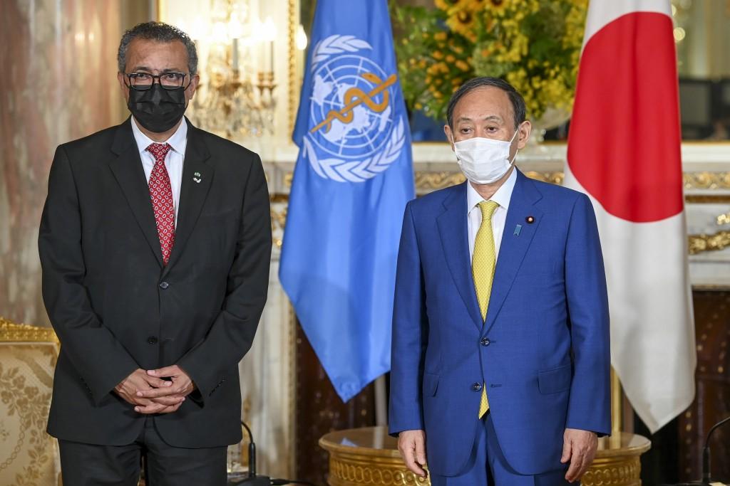 World Health Organization Director-General Tedros Adhanom Ghebreyesus, left, and Japanese Prime Minister Yoshihide Suga wearing face masks pose for a ...