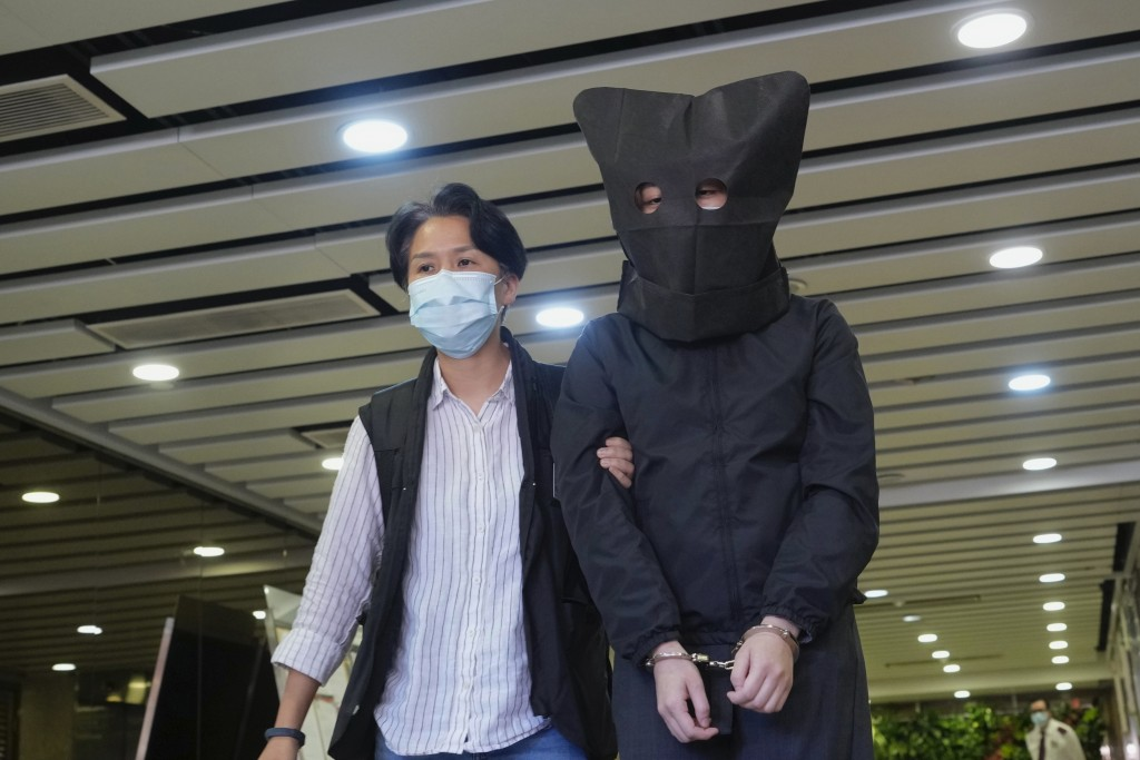 A hooded suspect is accompanied by a police officer to search evidence at office in Hong Kong Thursday, July 22, 2021. Hong Kong's national security p...