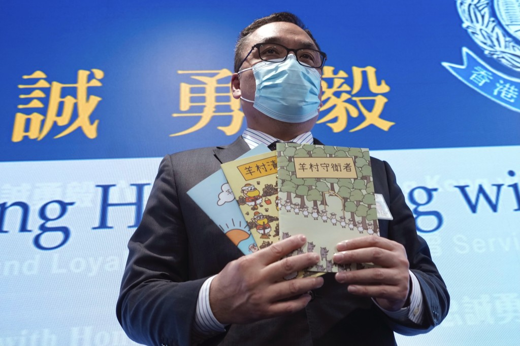 Li Kwai-wah, senior superintendent of Police National Security Department, poses with evidence including three children's books on stories that revolv...