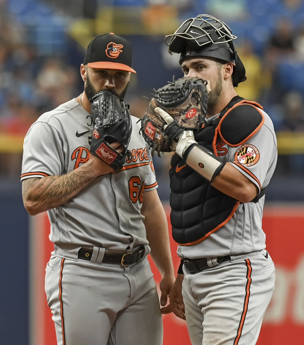 Baltimore Orioles catcher Austin Wynns, right, and reliever Tanner Scott (66) talk on the mound after loading the bases in the ninth inning of a baseb...