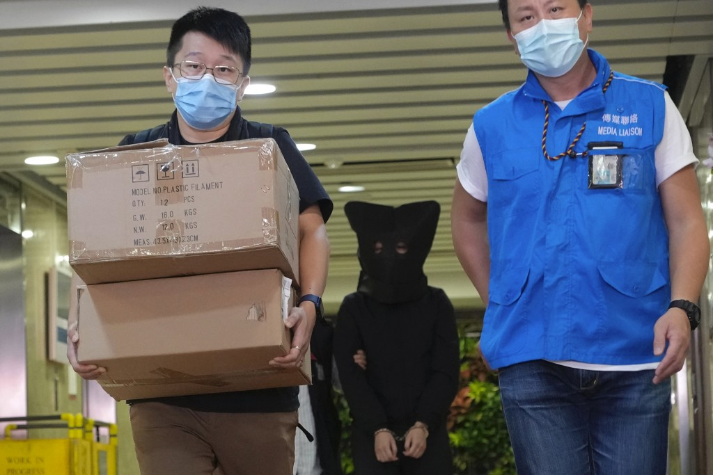 Police officers leave a building with a hooded suspect, center, after searching evidence in Hong Kong Thursday, July 22, 2021. Hong Kong's national se...