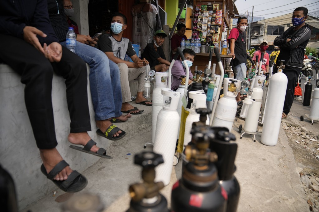 In this July 5, 2021, file photo, people queue up to refill their oxygen tanks at a filling station in Jakarta, Indonesia. Images of bodies burning in...