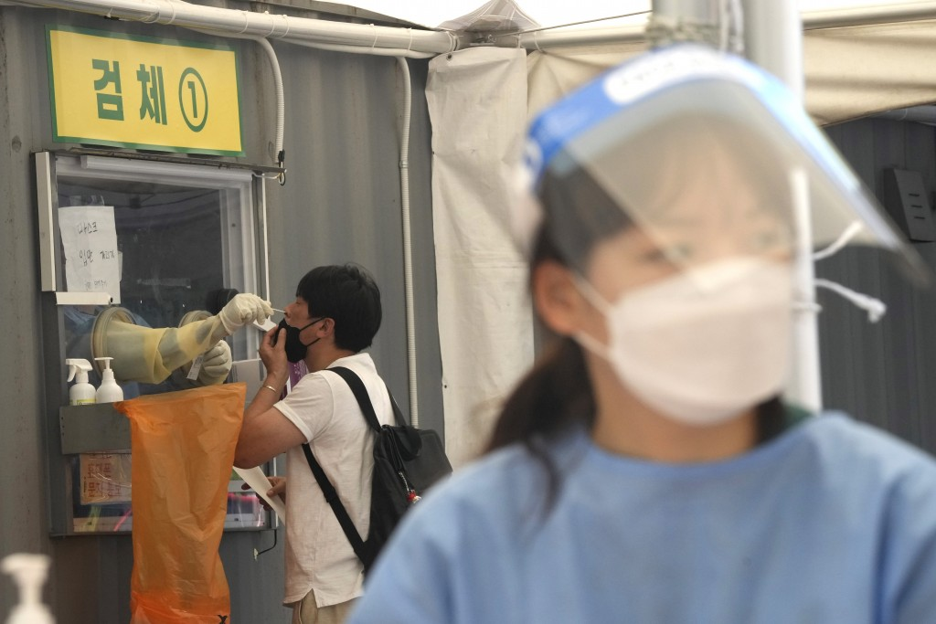 A medical worker in a booth takes a nasal sample from a man during coronavirus testing at a makeshift testing site in Seoul, South Korea, Thursday, Ju...