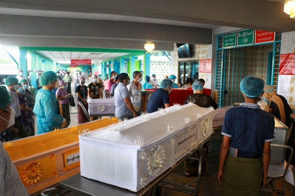 In this July 14, 2021, file photo, people wearing face masks wait while caskets with bodies are queued outside a crematorium at the Yay Way cemetery i...