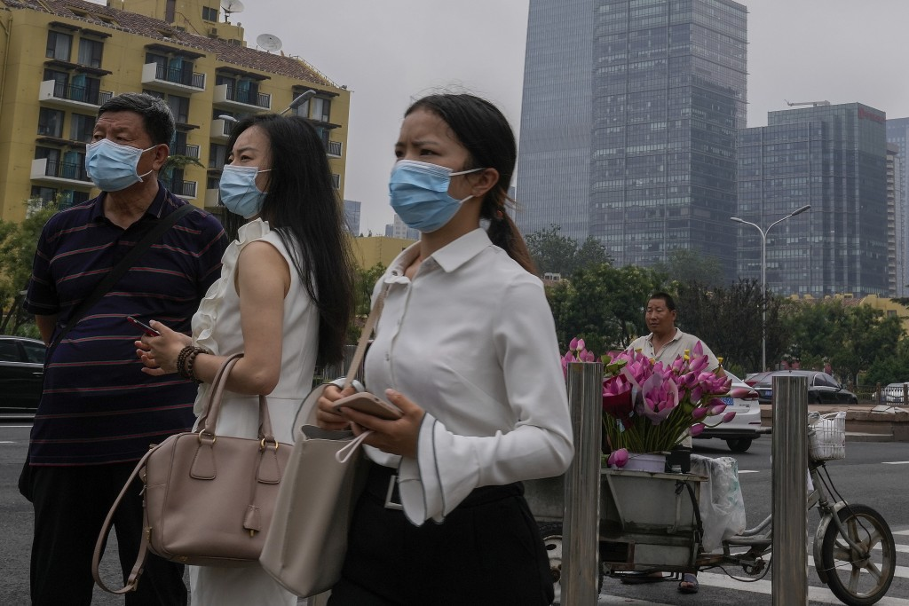 People wearing face masks to help curb the spread of the coronavirus stand watch near a vendor selling flowers outside a subway station in Beijing, Th...