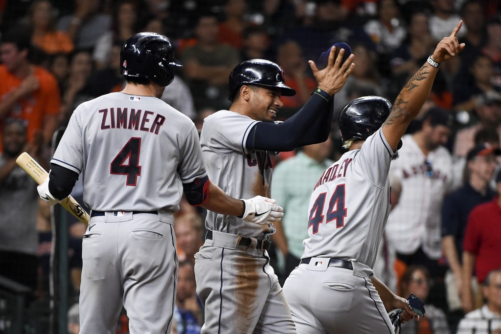 Cleveland Indians' Oscar Mercado, center, celebrates, after scoring a run on Ernie Clement's three-run double, with Bradley Zimmer (4) and Bobby Bradl...
