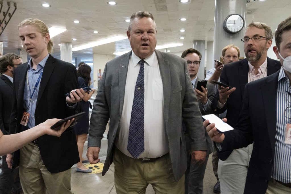 Sen. Jon Tester, D-Mont., talks to reporters as he walks to the Senate chamber ahead of a test vote scheduled by Democratic Leader Chuck Schumer of Ne...