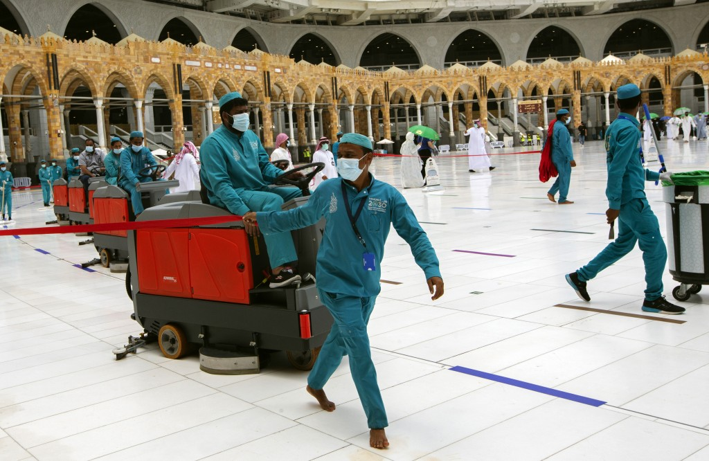 Workers disinfect the grounds at the Grand Mosque to help protect against the coronavirus in the Muslim holy city of Mecca, Saudi Arabia, Thursday, Ju...