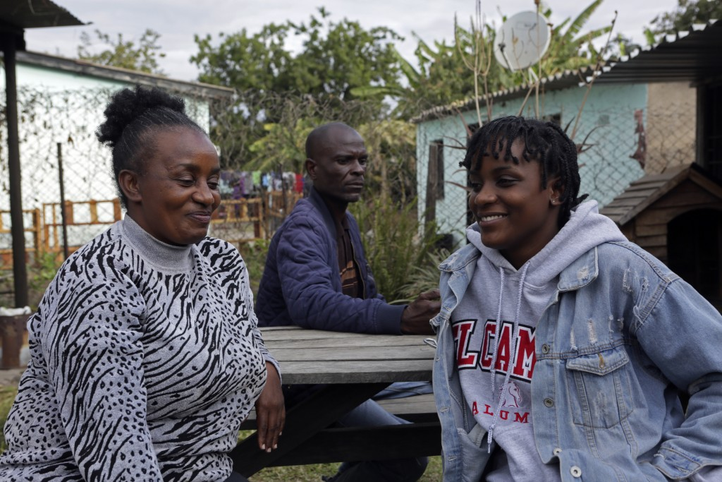 Andrew Ngwenya, center; his wife, De-egma, left, and their daughter sit outside their home in a working class township in Harare, the capital Zimbabwe...