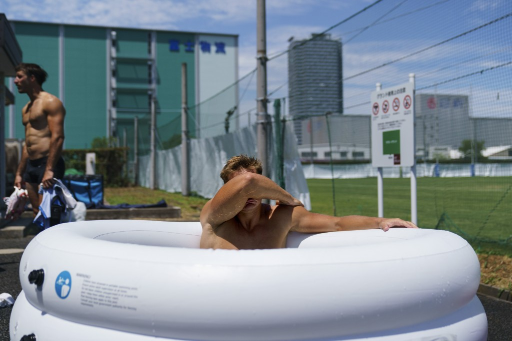 Argentina's Santiago Mare soaks in an ice bath following a men's rugby sevens practice at the Tokyo 2020 Olympics, in Tokyo, Friday, July 23, 2021. (A...
