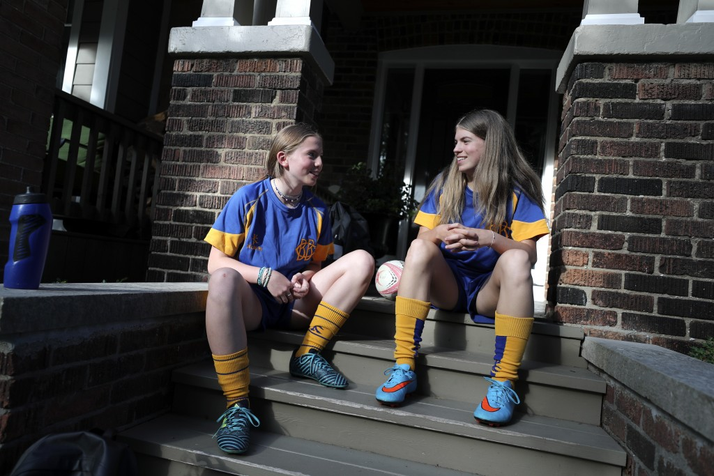 Ruby Wood, left, and her twin sister, Lola, talk on their home stoop in Toronto, Canada, on Monday, July 12, 2021. With Lola's aversion to needles, th...