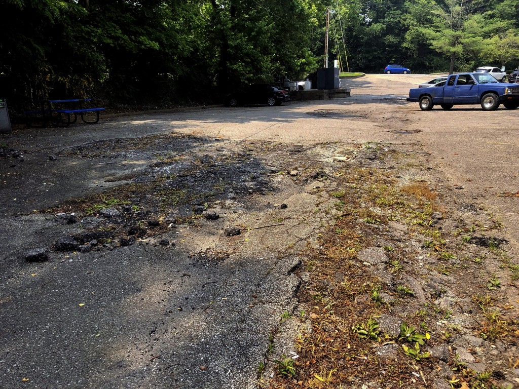 A crumbling parking lot at the Prestera Center headquarters is shown Wednesday, July 21, 2021 in Huntington, W. Va. In one of the epicenters of the U....