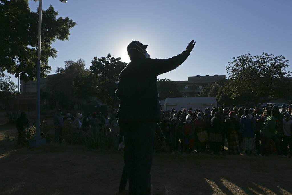 A security guard addresses a crowd at a government hospital after COVID-19 vaccines ran out in Harare, Zimbabwe, on Saturday, July, 10, 2021. Only abo...