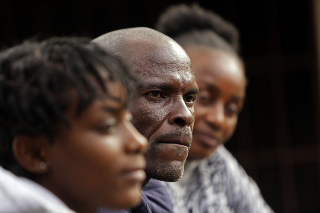 Andrew Ngwenya, center, and his wife, De-egma, right, and daughter sit outside their home in a working class township in Harare, the capital of Zimbab...