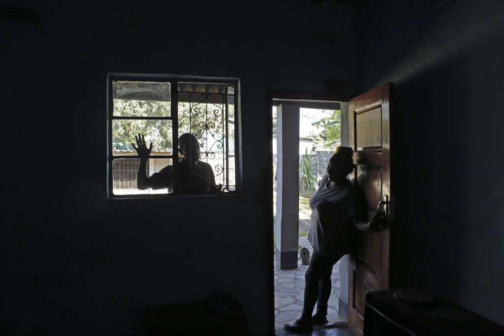 Andrew Ngwenya, left, and his wife, De-egma, are seen at their home in a working class township in Harare, the capital Zimbabwe, on Monday, July, 12, ...