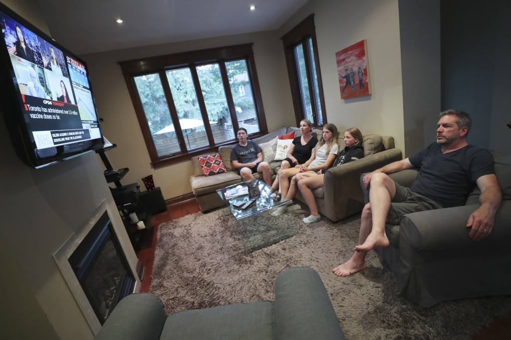 The Wood family, from left, Ethan, Amanda, Lola, Ruby and David, watch television at home in Toronto, Canada, on Monday, July 12, 2021. With nearly 70...