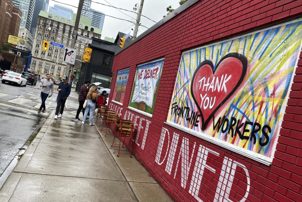 People line up to dine at a restaurant that has painted its walls to support the frontline workers in downtown Toronto, Canada, on Saturday, July 17, ...