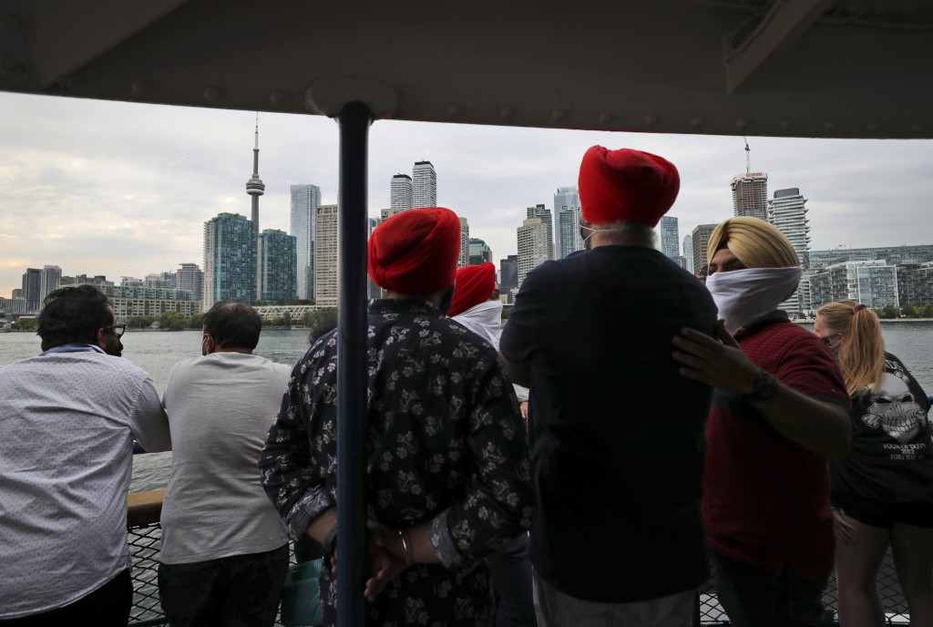 People look at the city skyline on a ferry coming back from Centre Island to Toronto, Canada, Saturday, July 17, 2021. With nearly 70% of its adult po...