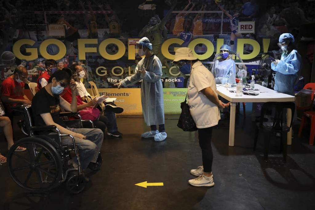 Medical workers brief persons about their vaccination cards after receiving a shot ofCOVID-19 vaccine (AP photo)