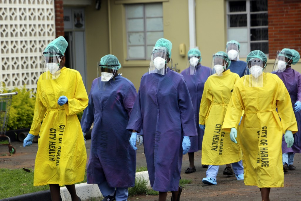FILE - In this Thursday, Feb, 18, 2021 file photo, health workers walk together at a hospital where China's Sinopharm vaccine was being administered i...