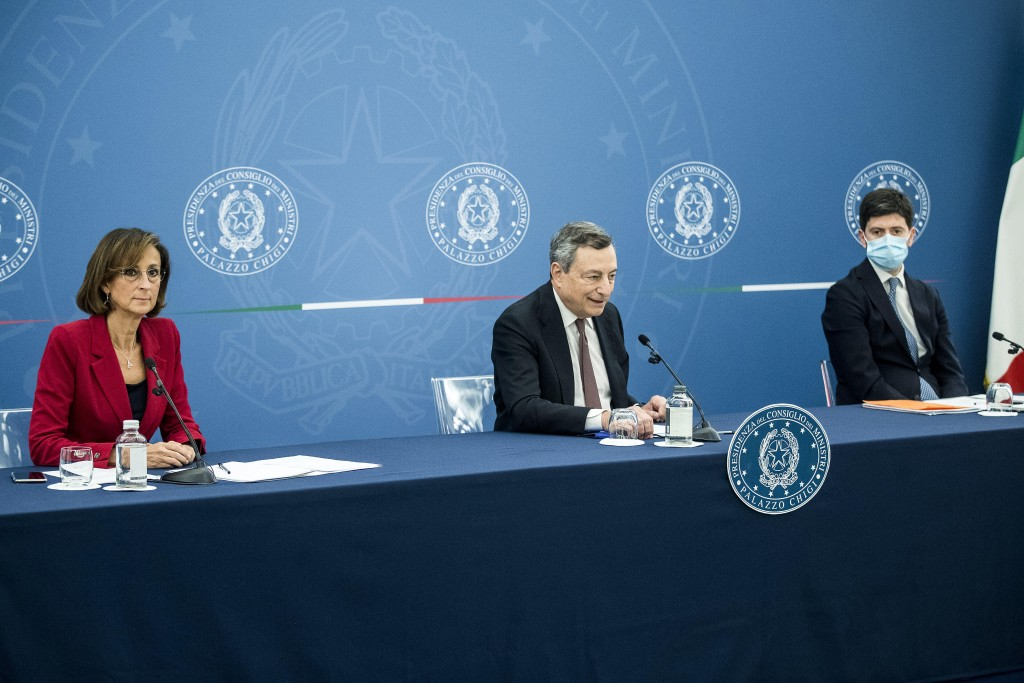 Italian Premier Mario Draghi, center, sits beside Justice Minister Marta Cartabia, left, and Health Minister Roberto Speranza during a press conferenc...