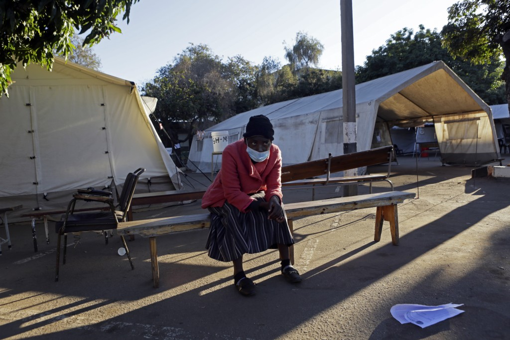 A woman sits on a bench while pondering her next move after COVID-19 vaccines ran out at a government hospital in Harare, Zimbabwe, on Saturday, July,...
