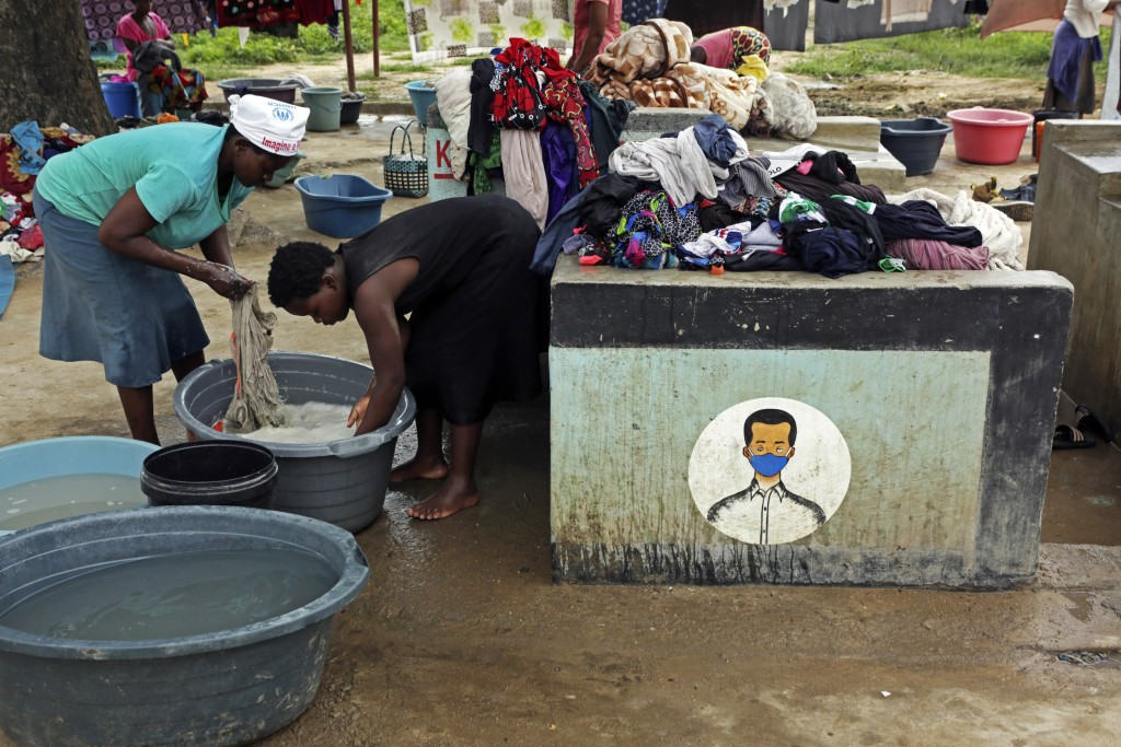 FILE - In this Thursday, March 4, 2021 file photo, women do laundry next to signs urging them to wear face masks to prevent the spread of COVID-19, at...
