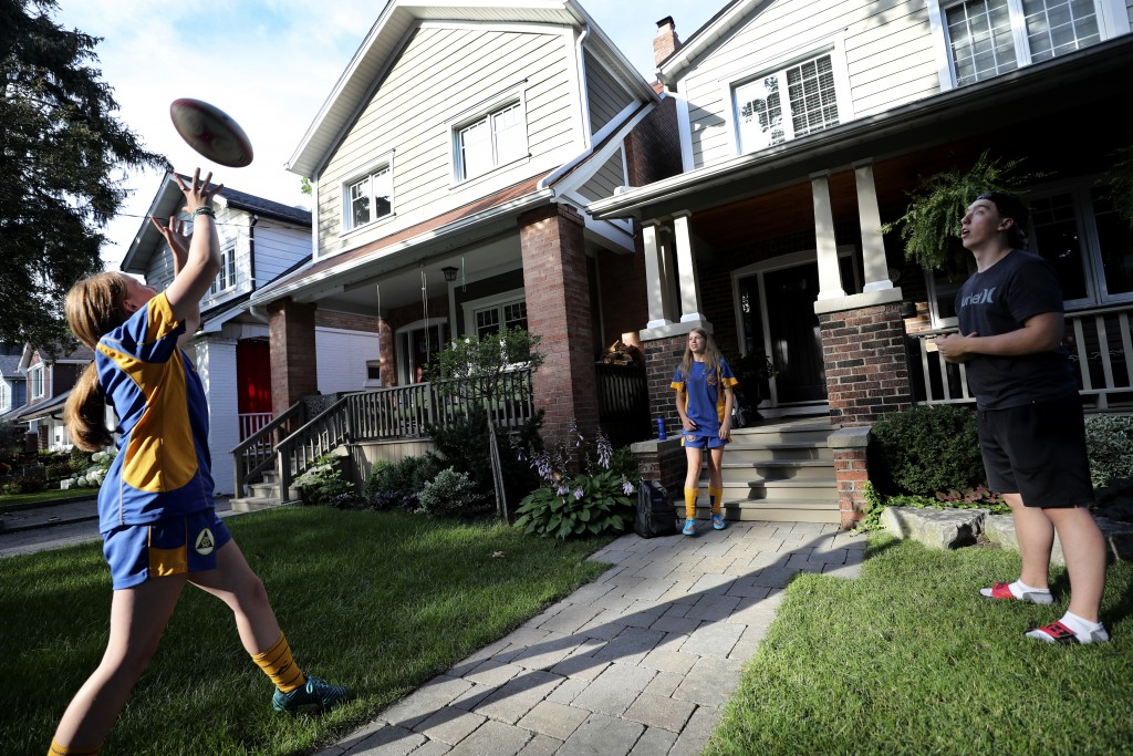 Ruby Wood, left, and her twin sister, Lola, practice rugby with their brother, Ethan, in front of their home in Toronto, Canada, on Monday, July 12, 2...
