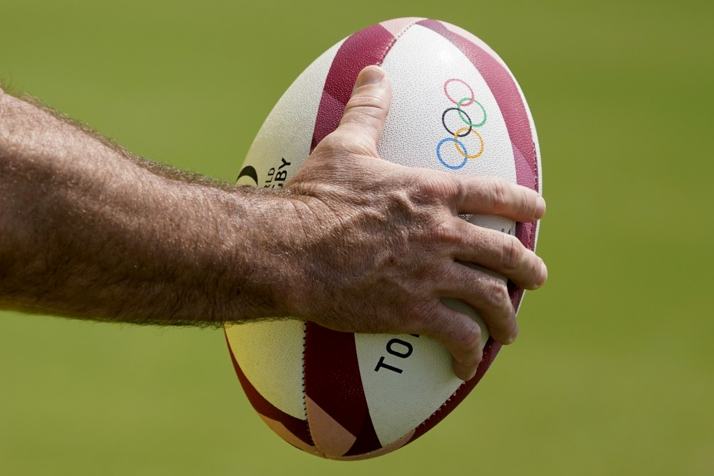 A member of Australia's men's rugby sevens team holds a ball during a practice at the Tokyo 2020 Olympics, in Tokyo, Friday, July 23, 2021. (AP Photo/...