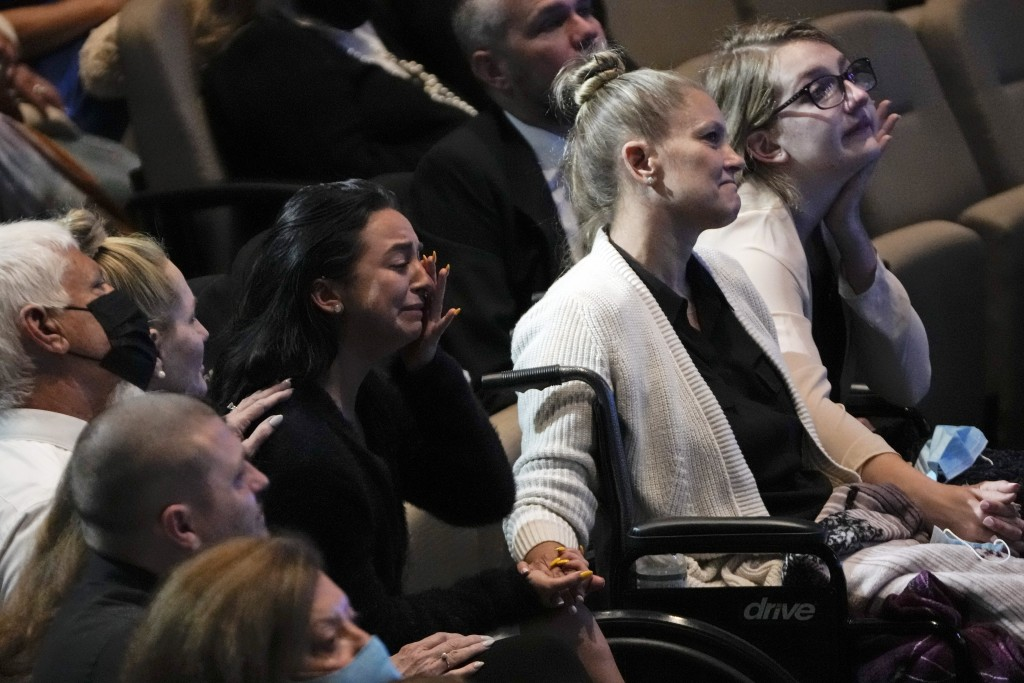 Angela Gonzalez, center right, holds hands with her daughters Tayler Scheinhaus, center left, and Deven Gonzalez, right, during the funeral service fo...