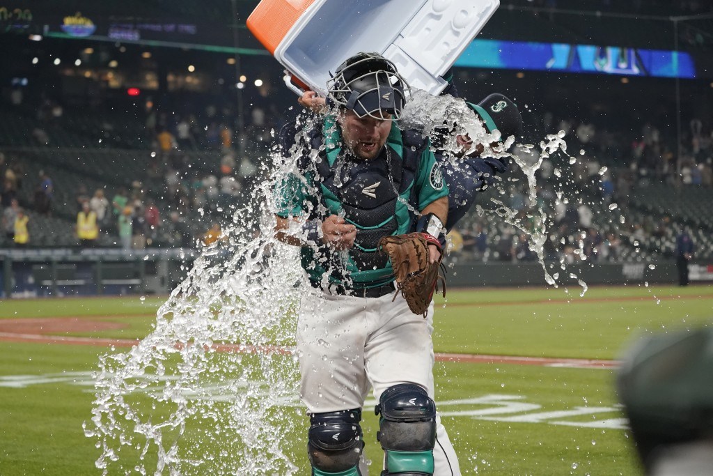 Seattle Mariners catcher Cal Raleigh has water and ice dumped onto him by teammate Tom Murphy as Raleigh takes part in an interview after the Mariners...