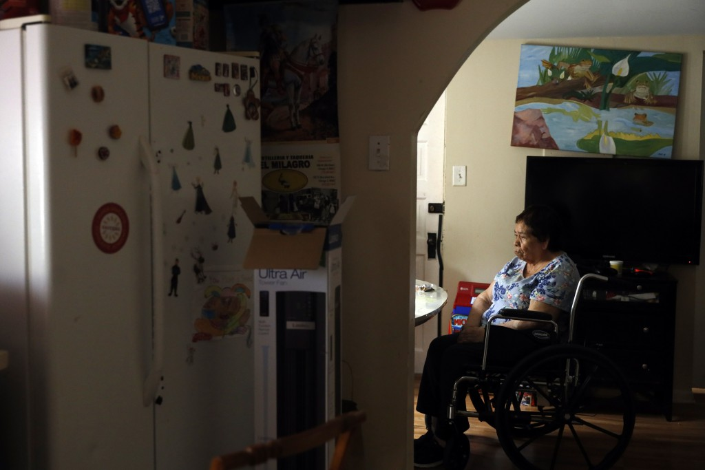 Francisca Perez, 84, sits by the dining table on a wheelchair in her house in Chicago's Little Village neighborhood, Wednesday, June 30, 2021. She suf...