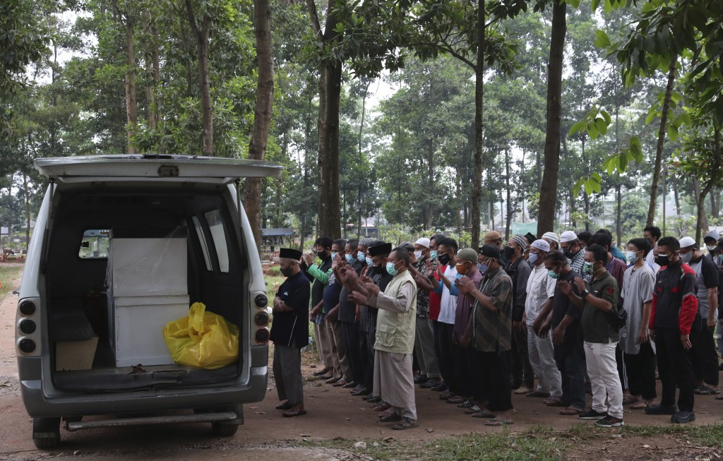 Residents pray near an ambulance carrying coffins of COVID-19 victims prior to a burial at Cipenjo cemetery in Bogor, West Java, Indonesia on July 14,...