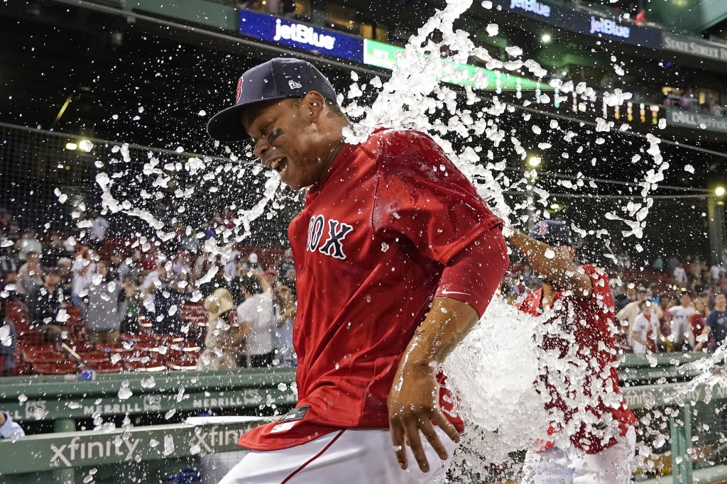 Boston Red Sox's Rafael Devers is doused with ice water to celebrate the team's 6-2 victory over the New York Yankees in a baseball game at Fenway Par...